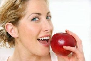 Woman smiles as she takes bite of apples