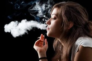 Young girl blowing cloud of smoke