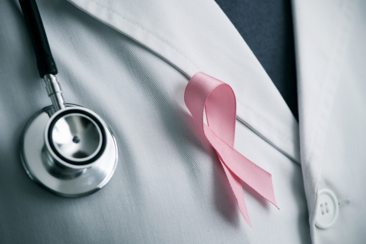 closeup of a young caucasian doctor man with a pink ribbon for the breast cancer awareness pinned in the flap of his white coat