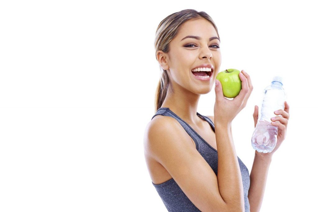 Athletic woman smiles while holding bottle of water and apple