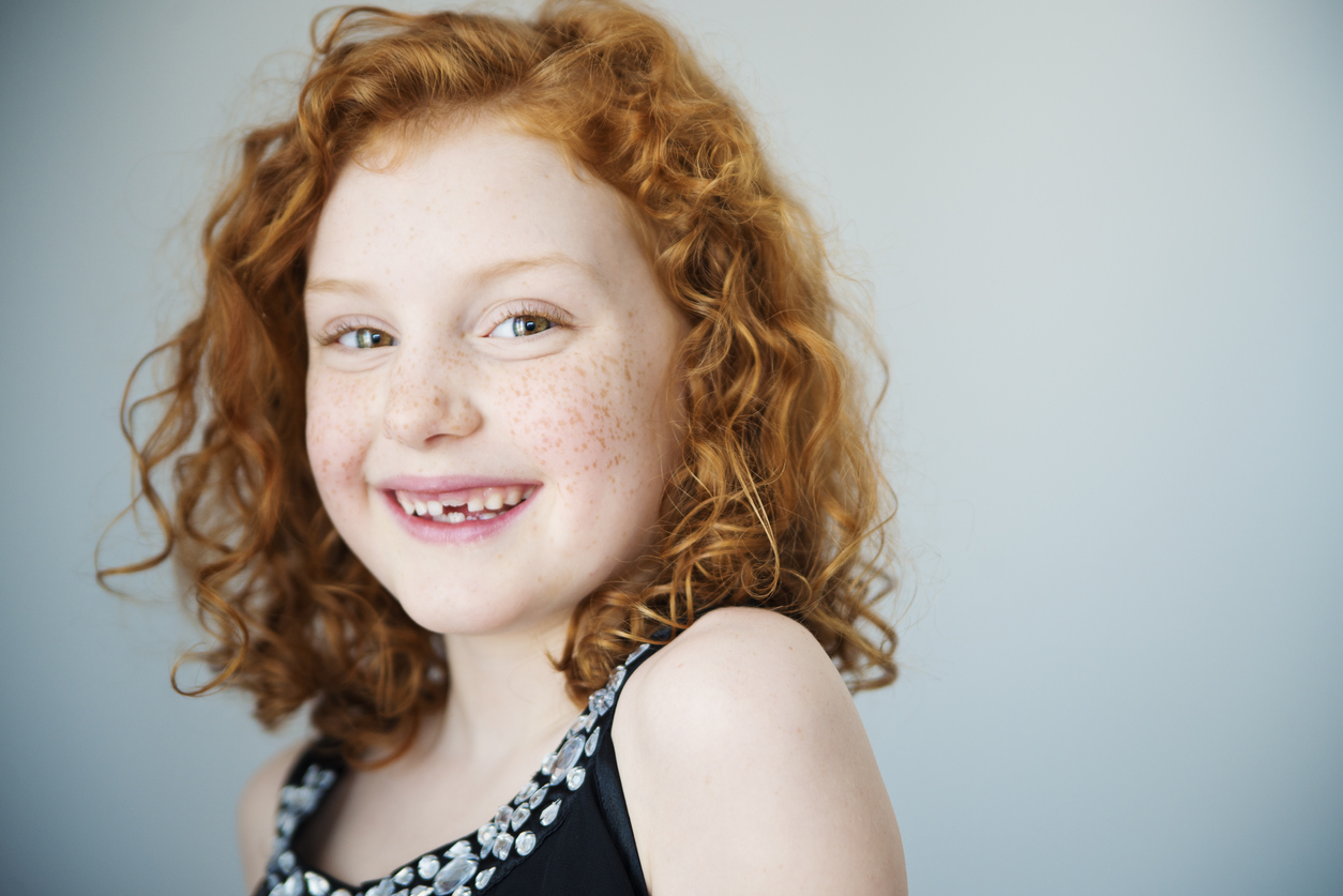 Portrait of a smiling little girl with flamboyant redhead and a missing tooth. She has curly hair and is looking at the camera. Light gray background. Focus on one eye. Horizontal indoors head and shoulders shot with copy space. This was shot in Quebec, Canada.