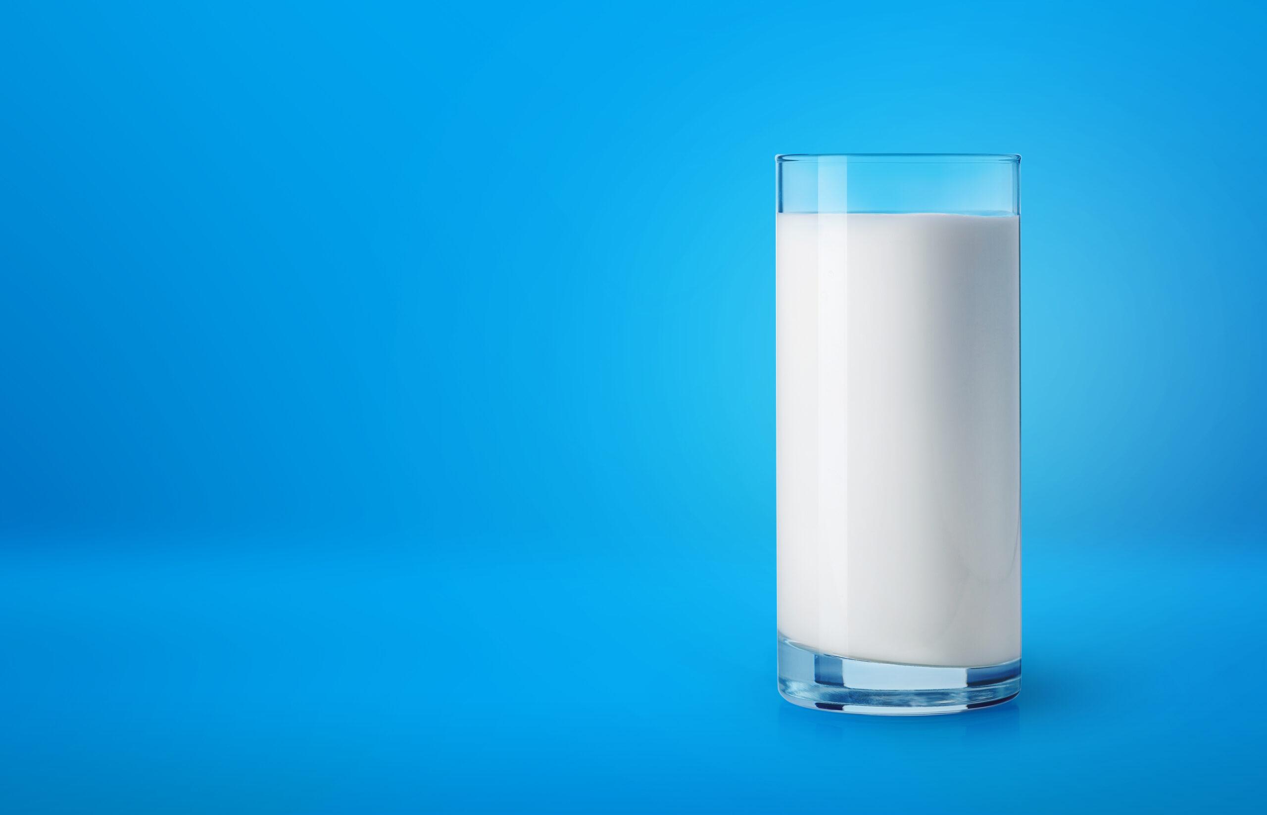 Glass of fresh milk on blue background